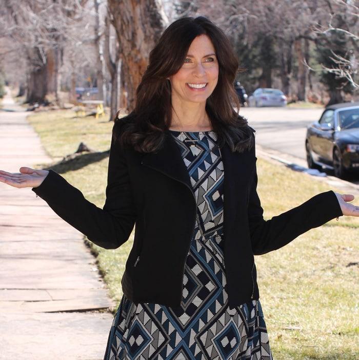 Ana wearing a black blazer jacket over a printed dress   40plusstyle.com
