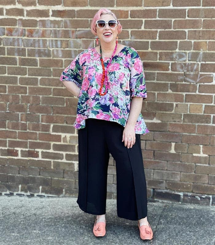Pants to hide a belly - Kim wears a floral top with black pants   40plusstyle.com