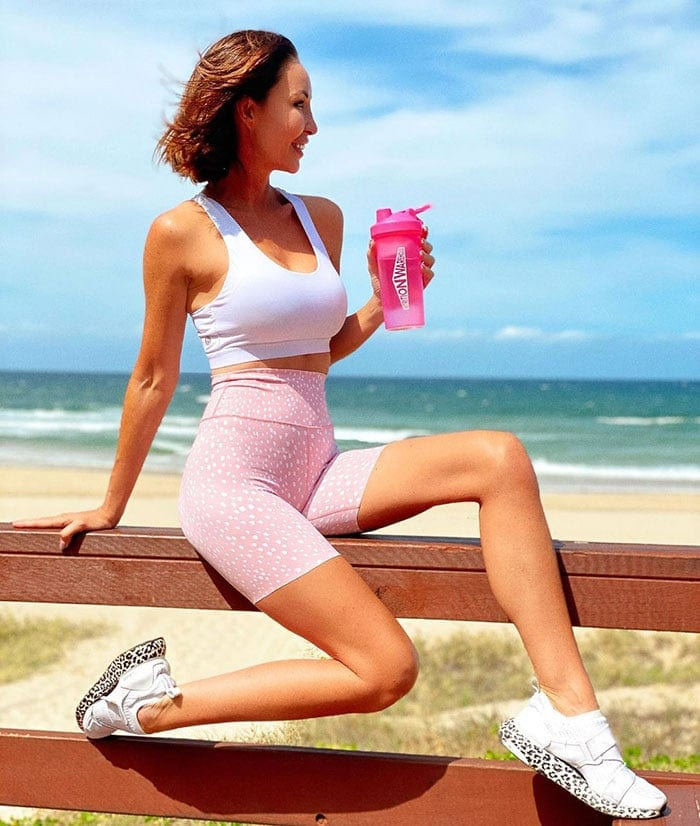 Best workout clothes for women - Eve wears pink shorts and leopard print sneakers