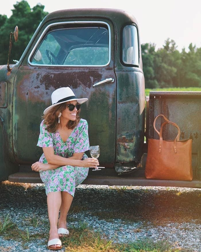 Carelia wearing floral dress and sun hat | 40plusstyle.com