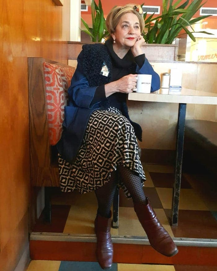 Terrie wearing coat, printed skirt with tights and booties| 40plusstyle.com