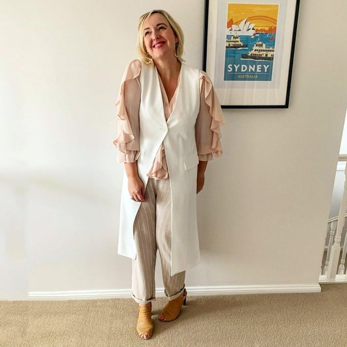 wearing a ruffle blouse and neutral striped pants | 40plusstyle.com