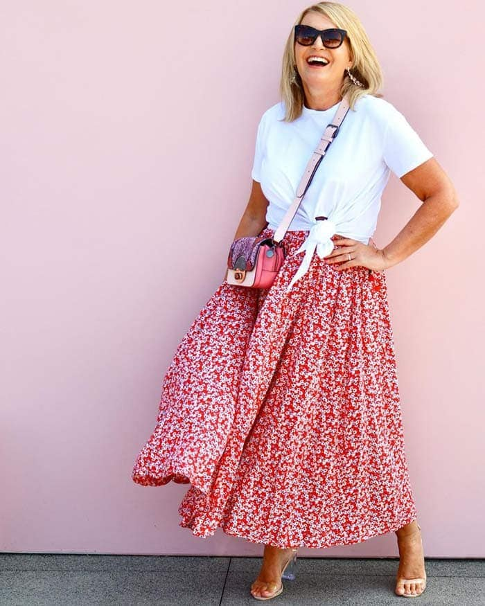 an elastic waist red floral skirt worn with a white knotted t-shirt | 40plusstyle.com
