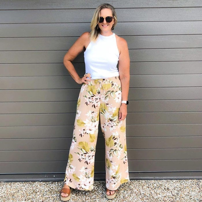 a pair of patterned floral pants with a white top | 40plusstyle.com