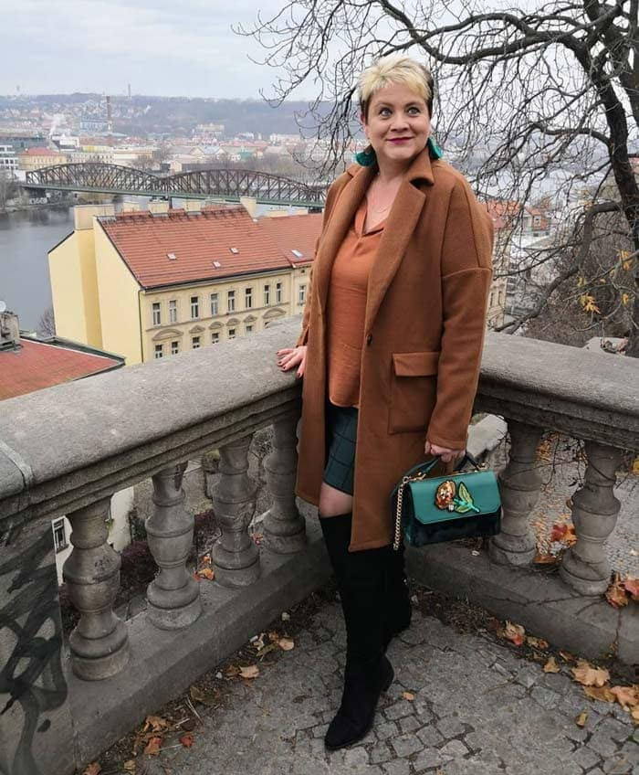 Lucie wearing a beige outfit with green accessories | 40plusstyle.com