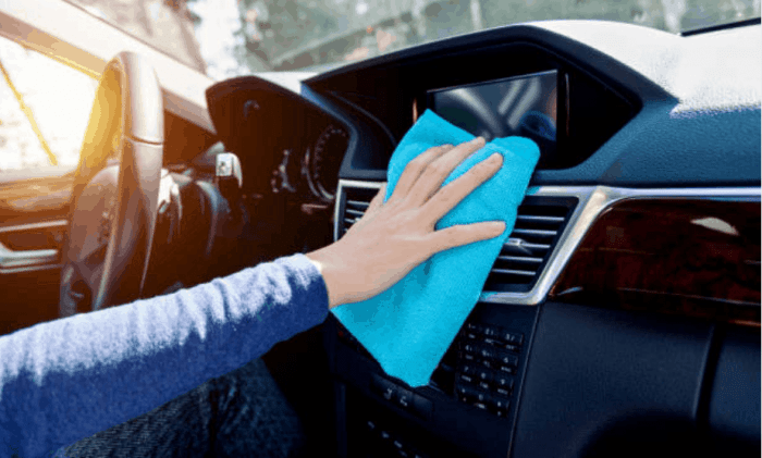 white female hand wiping a car's dashboard with a blue cloth.