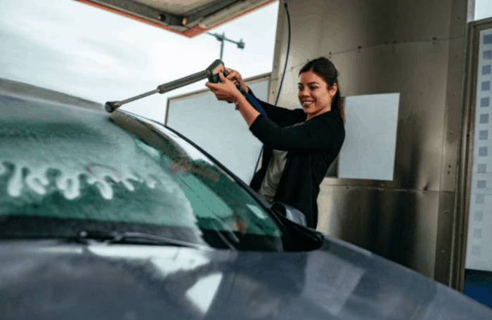 a white female woman washing a car with a spray hose in a covered area.