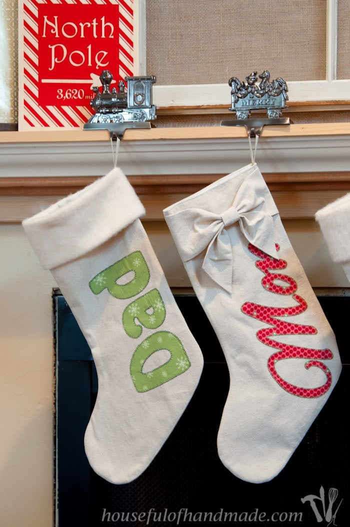 two DIY personalized drop cloth Christmas stockings hanging on fireplace mantel.