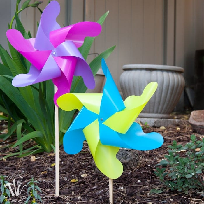 set of two pinwheels in the garden in front of planter and green plant.