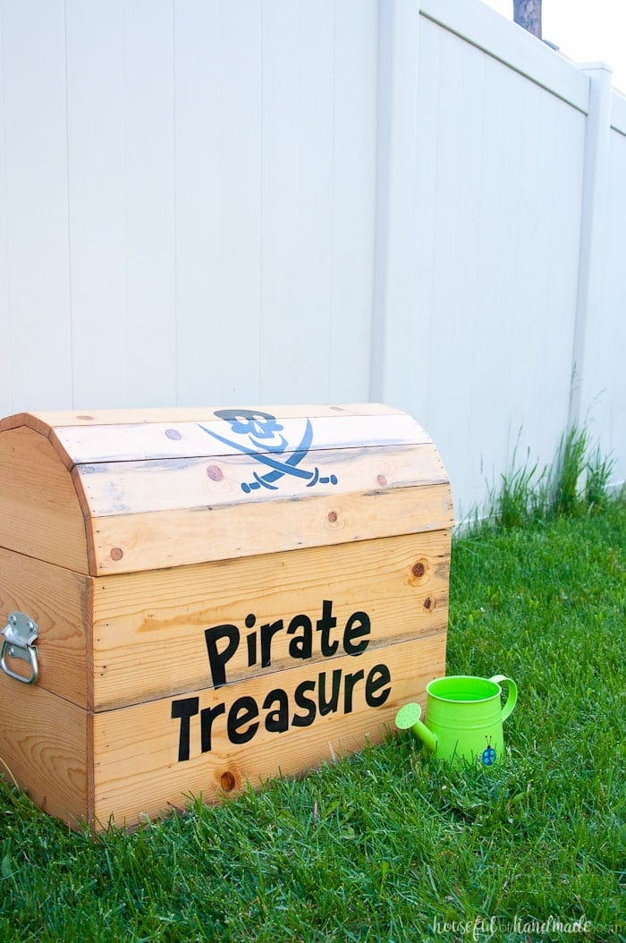 DIY treasure chest toy box shown outside with green watering can.