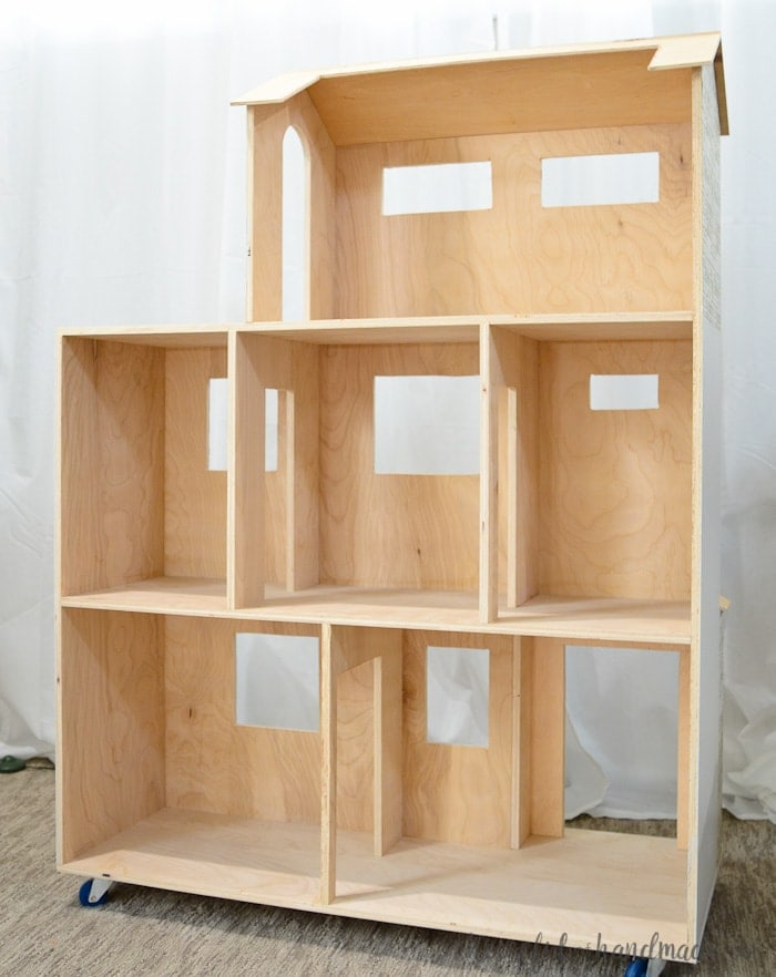 "Use these handmade dollhouse plans to make the perfect Christmas present this year. The 4' dollhouse is built out of plywood for a sturdy house that will last. Large rooms are big enough for 11"" dolls, and they can even to fit through the door ways standing up. A DIY dollhouse is the perfect surprise for Christmas morning! Housefulofhandmade.com"