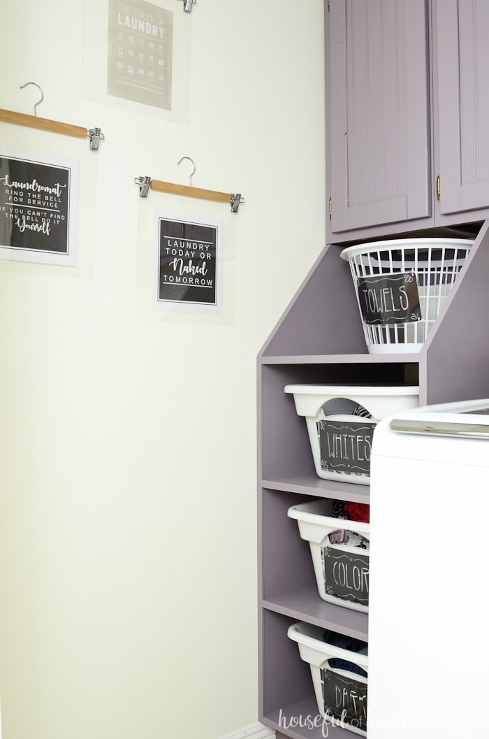 Purple stacking laundry basket storage with labeled laundry baskets. Art on the wall being hung with wooden pants hangers in a farmhouse laundry room. Housefulofhandmade.com