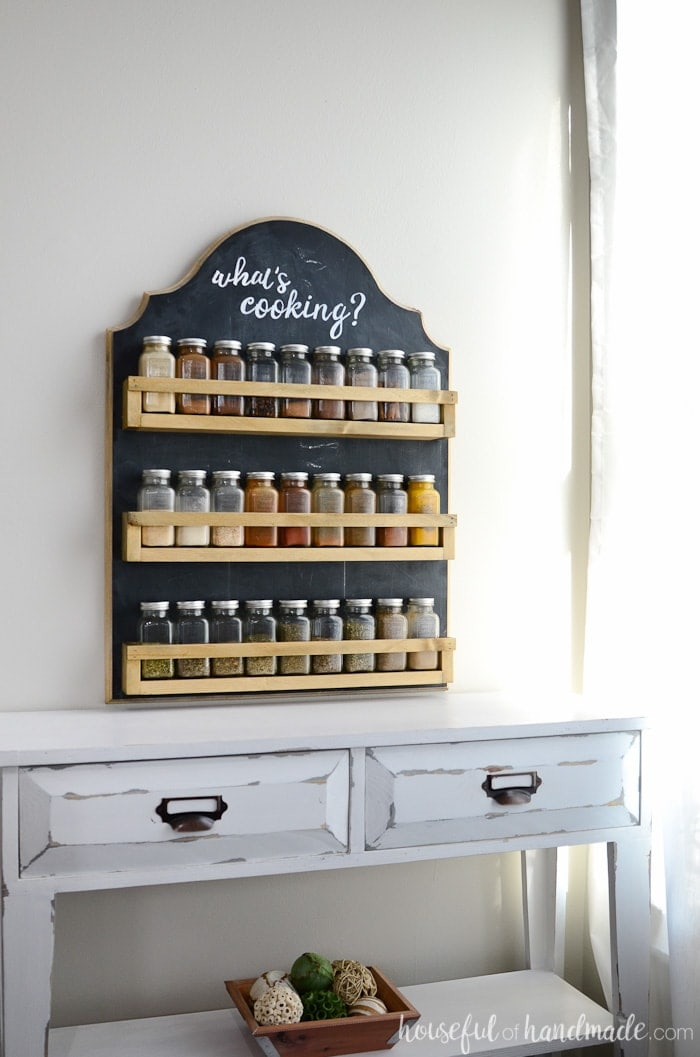 Hanging spice rack shown hanging on wall with glass spices