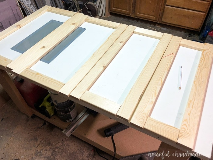 1x3 wood boards cut to length to build cabinet doors on a table in a garage workshop. Housefulofhandmade.com