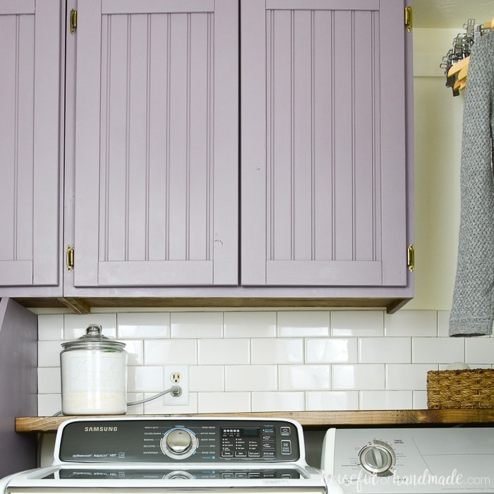 DIY cabinet doors with beadboard center panels painted purple. On cabinets above a washer and dryer.