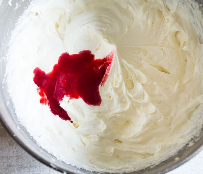 Cream cheese frosting in bowl with raspberry puree added