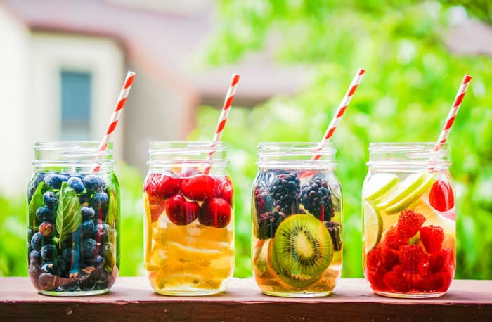 Mason jars of water with fruit in it