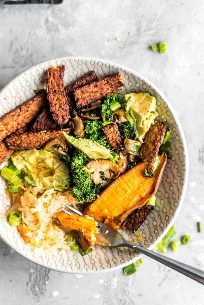 Cooked tempeh bacon, avocado, roasted sweet potato, sauerkraut, kale and mushrooms in a breakfast bowl.