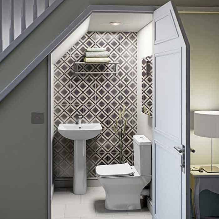 Toilet and sink fitted nicely under staircase