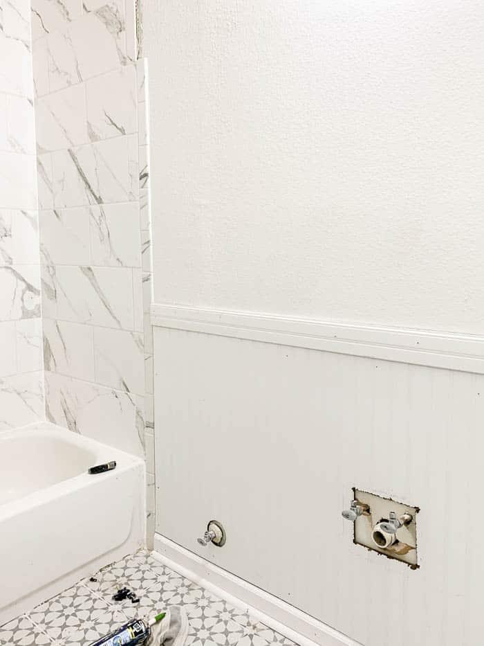 bathroom with beadboard paneling installed on lower half of walls