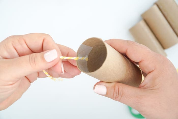 tape string to toilet paper inside