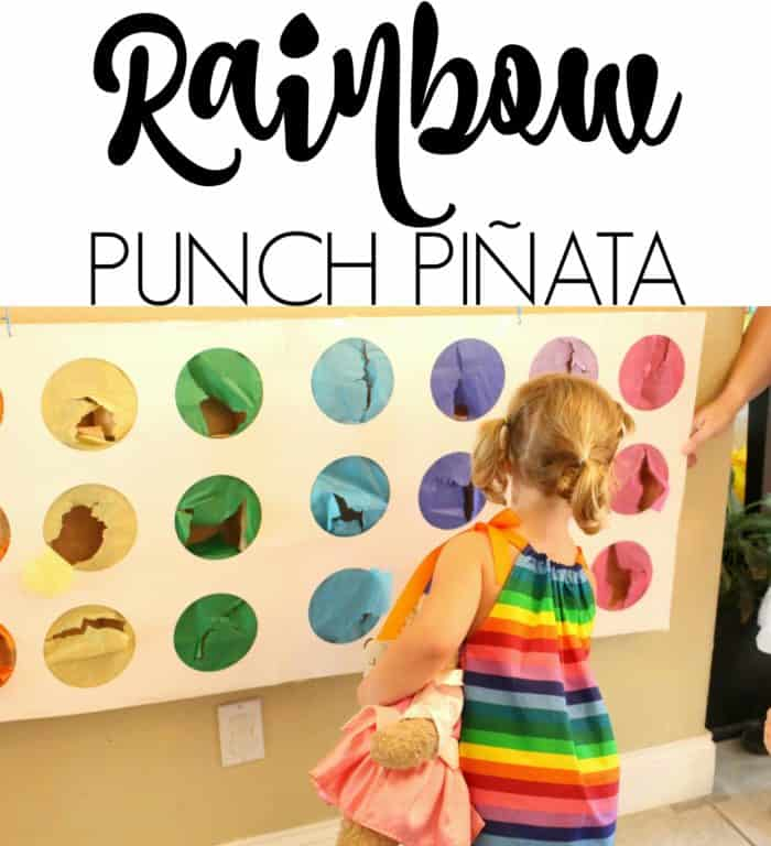 Child playing with rainbow punch pinata at rainbow party
