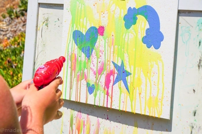 Painting with a water gun. Water gun painting. Looking for Summer activities for the kids? The kids LOVE water gun painting throughout the Summer.