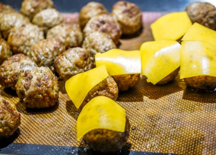 Adding cheese to your cocktail meatballs. These cheeseburger meatballs are our favorite cocktail meatball recipes. Serve these mini burgers or any cocktail meatball at your Superbowl party.