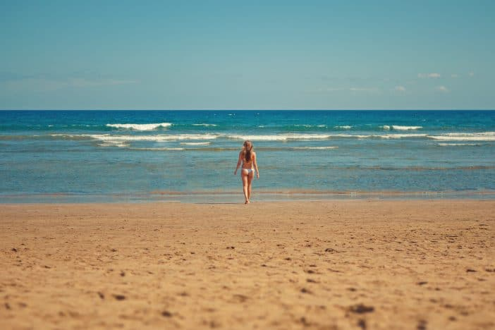 A Girl in a Swimwear Walking Towards an Isolated Beach