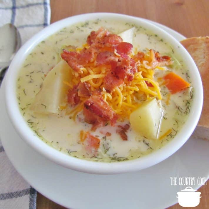 Slow Cooker Leek and Potato Soup topped with shredded cheddar and cooked bacon crumbles served in a white bowl with a chunk of bread