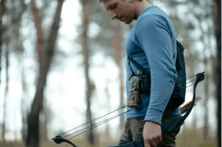carrying a bow with one hand in the woods