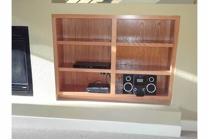 Custom built-in media shelving with stained wood in remodel of living room in Denver