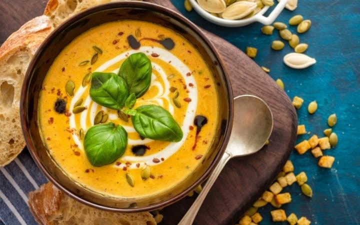 pumpkin soup with basil garnish resting on a wooden cutting board with a slice of rustic bread beside it making it one of the perfect fall soup recipes