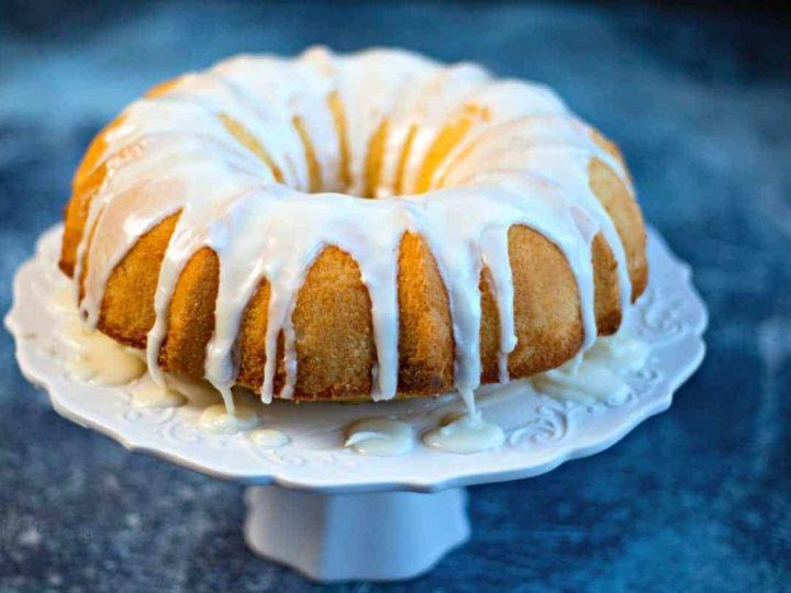 Lemon Bundt Cake with lemon glaze on a white cake stand