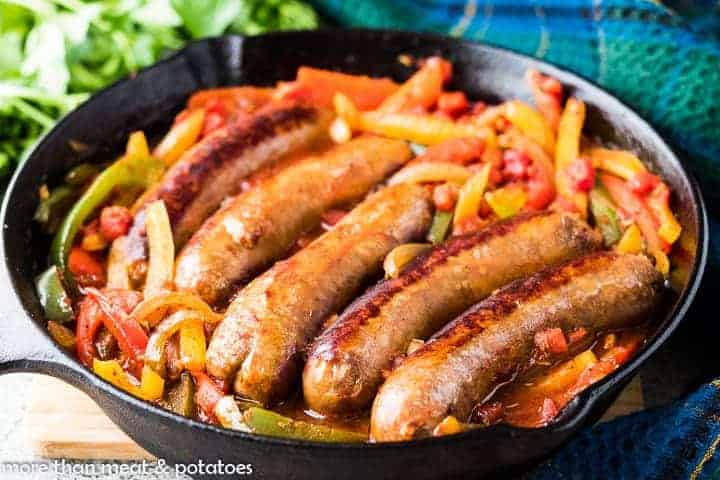 Italian sausage and cooked peppers in an iron skillet.