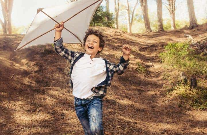 Best Outside Toys for Boys age 6-10. Boy playing outside with kite.