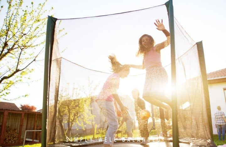 Kids jumping and playing games on a trampoline.