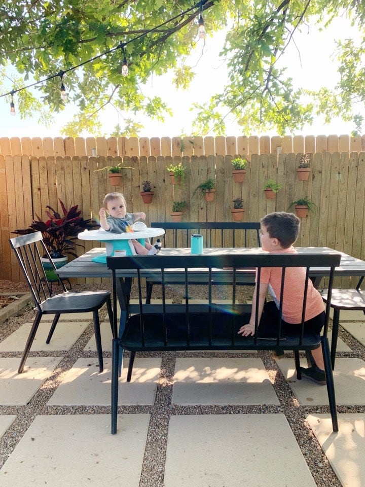 pea gravel patio with two young boys at a dining table