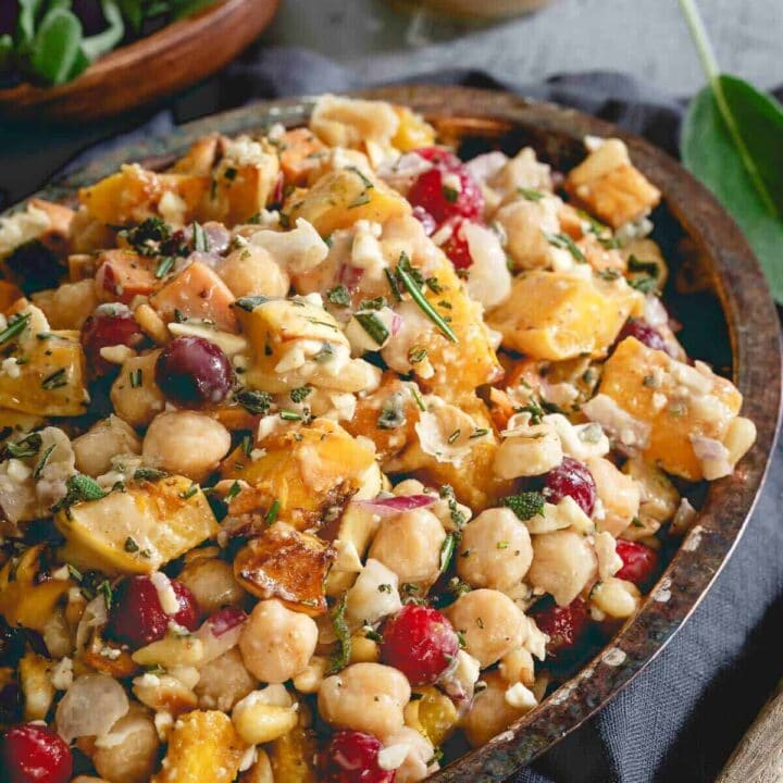 This chickpea fall salad is a hearty vegetarian meal with roasted sweet potatoes, delicata squash, cranberries, feta and a maple tahini dressing.
