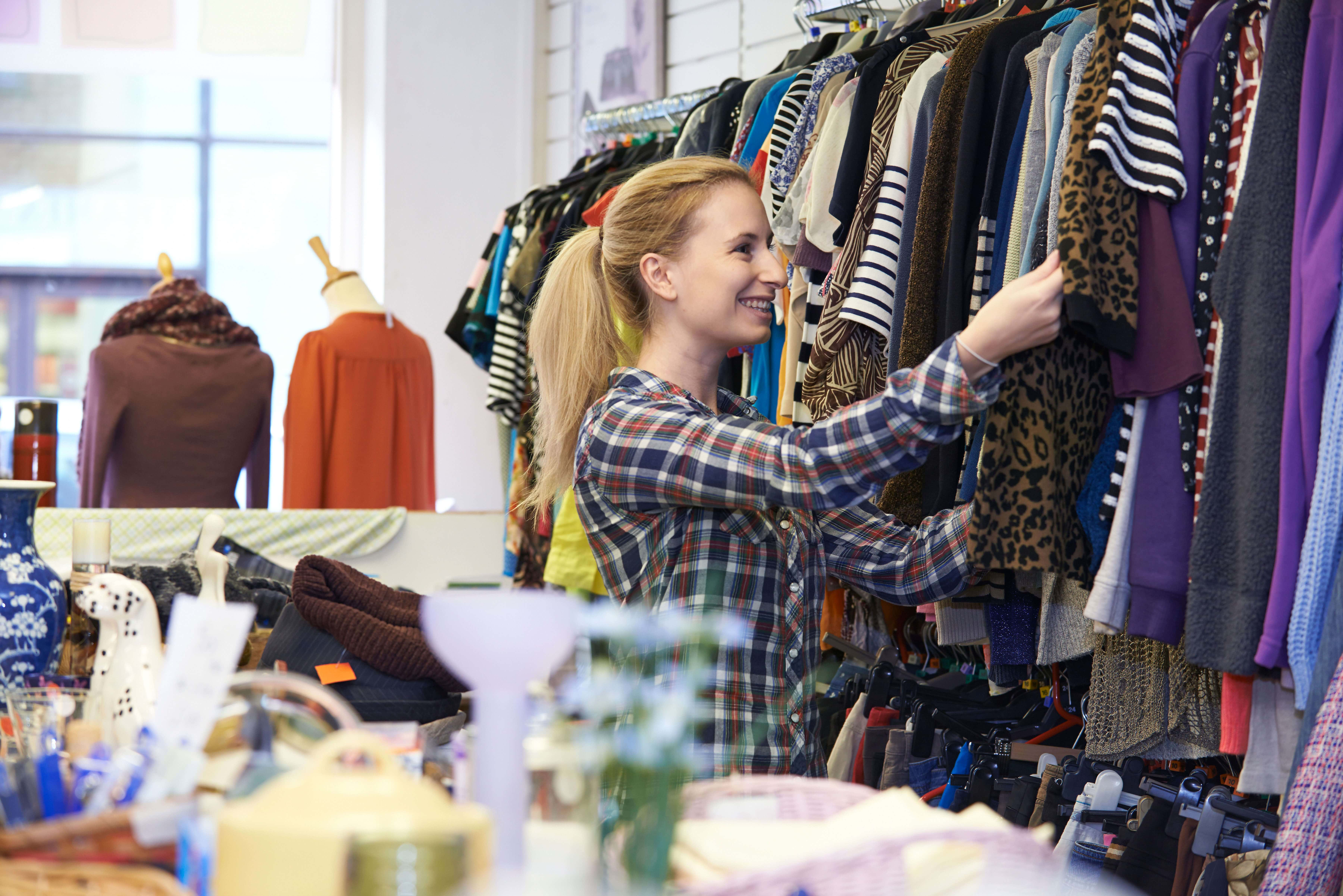 woman looking through clothing at a thrift store