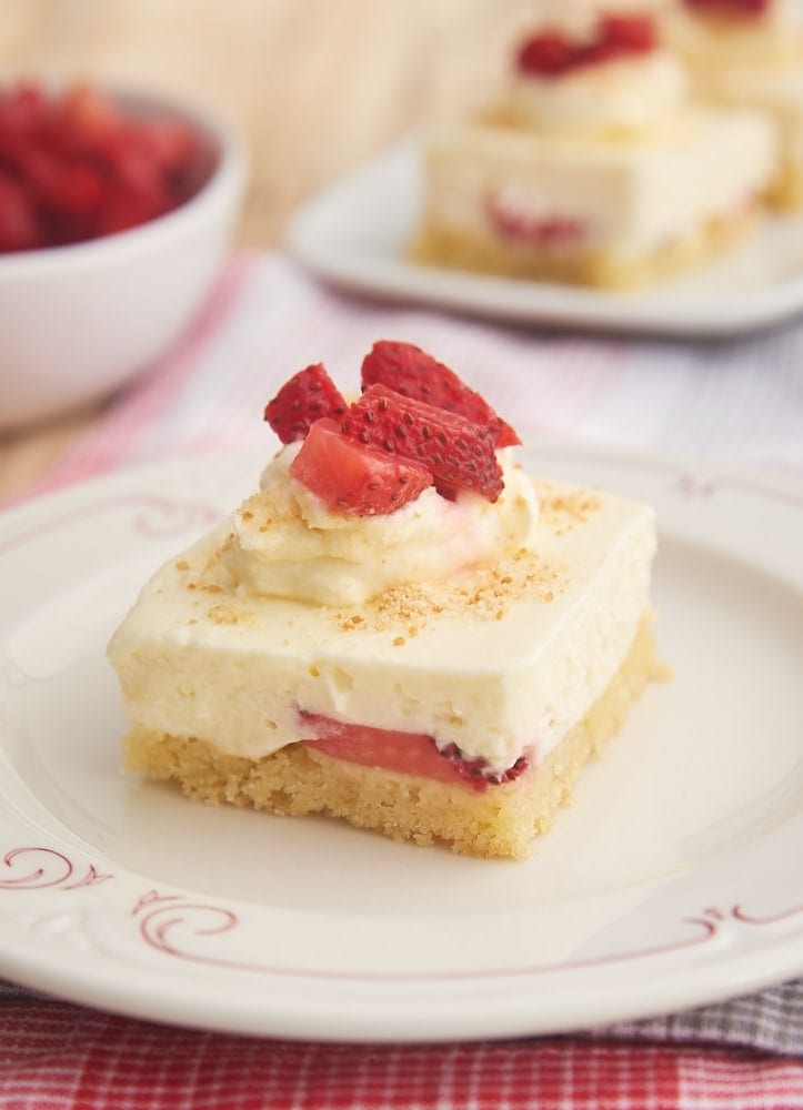 Strawberry Shortcake Cheesecake Bars on a white plate with a red decorative design around the outside