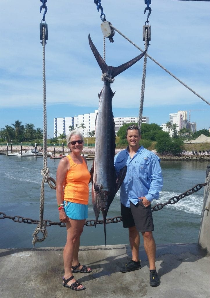 Stacey Wittig stands next to Blue Marlin fish and fisherman