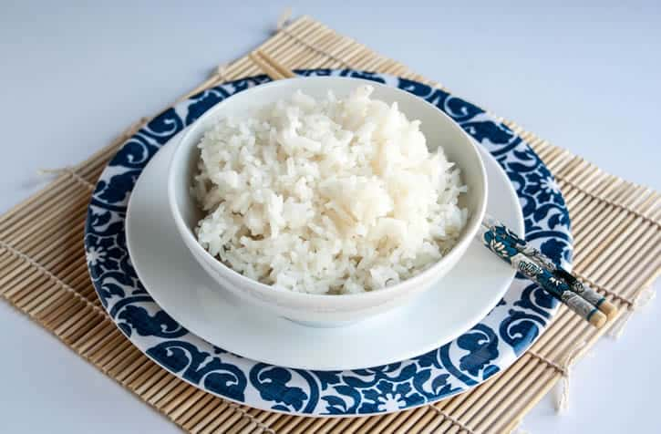 An image of a bowl of Perfect White Rice with chopsticks from themerchantbaker.com