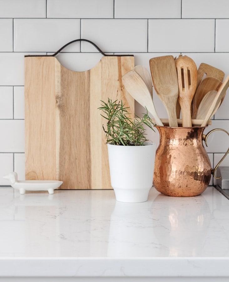 cutting board, rosemary plant, copper utensil holder