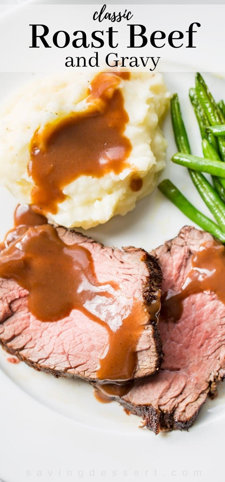 A plate filled with classic roast beef and gravy with mashed potatoes and green beans