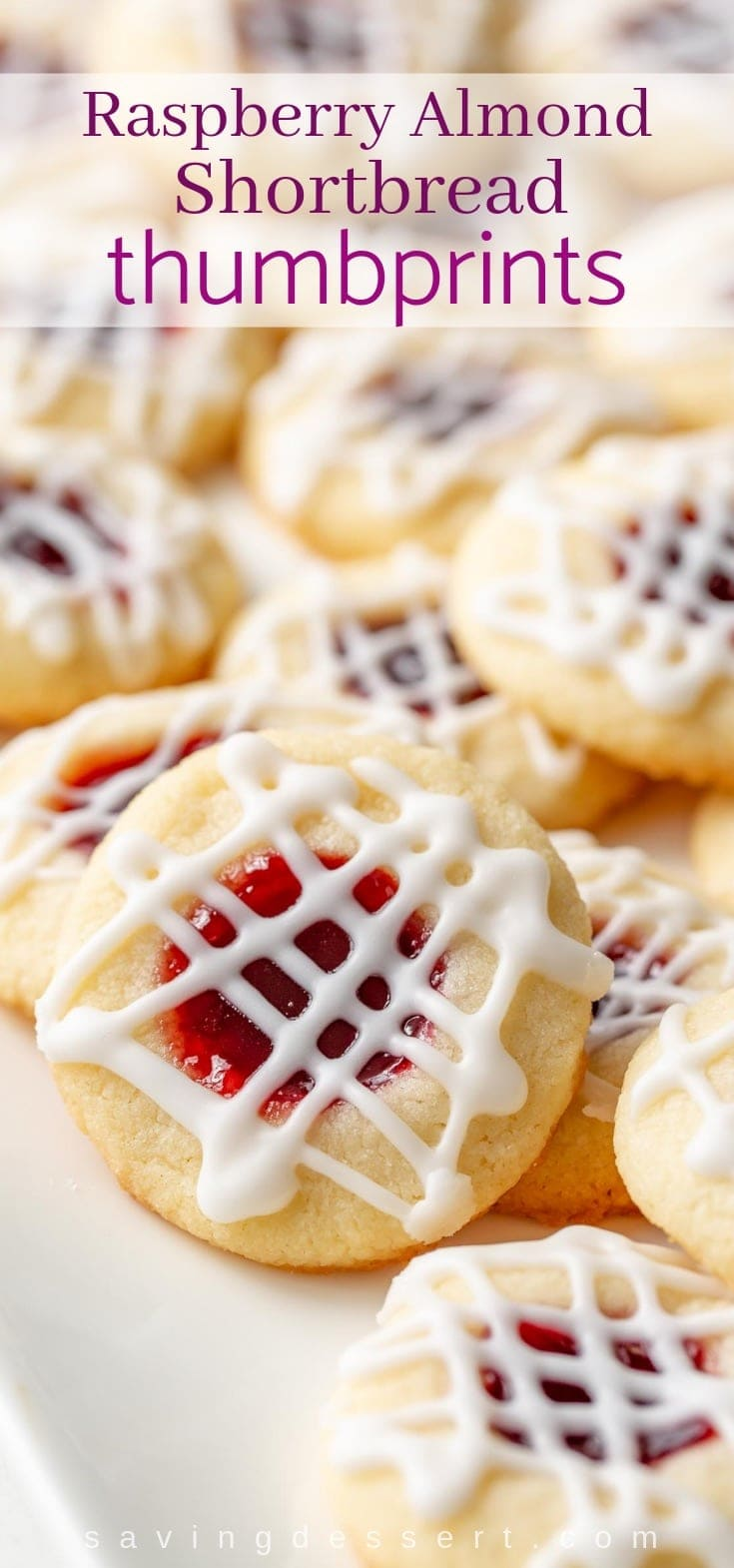 A plate of Raspberry Almond Shortbread Thumbprint Cookies with a drizzle of almond icing