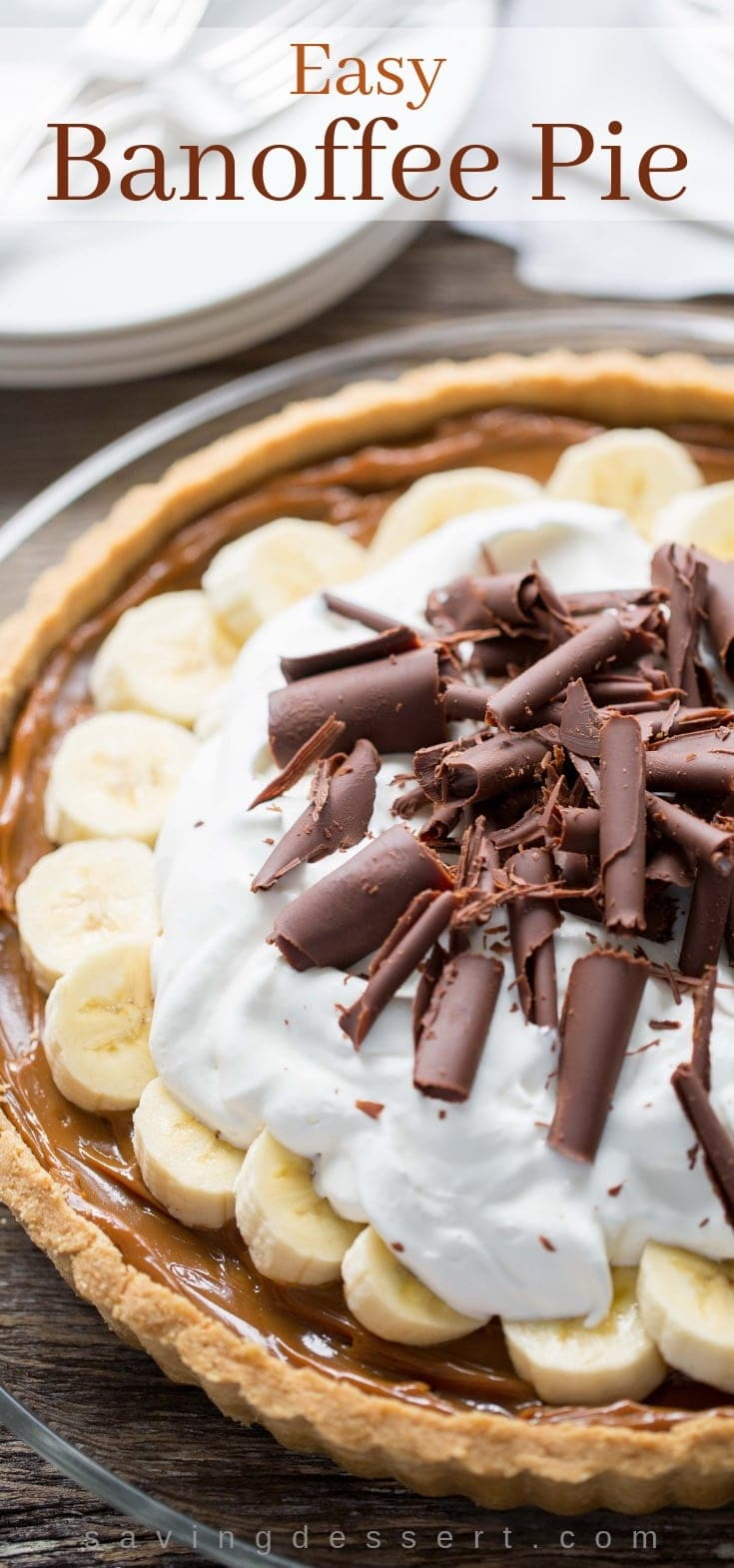 Banoffee Pie topped with whipped cream, bananas and chocolate curls