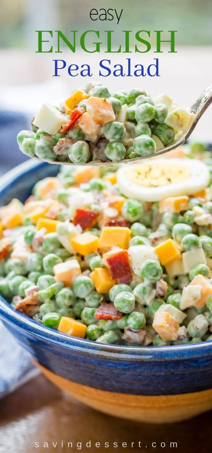 A bowl of English pea salad with peas, cheddar cheese, bacon, red onion and hard boiled eggs