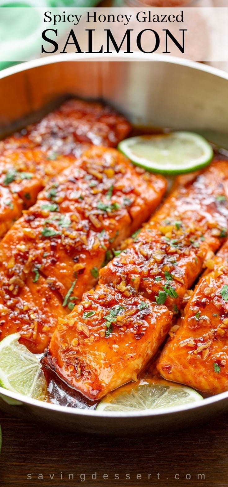 A skillet with Spicy Honey Glazed Salmon garnished with sliced lime