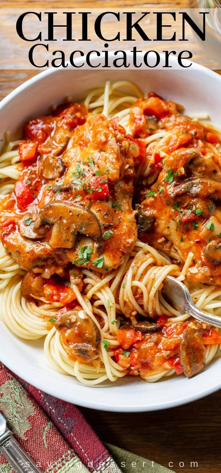 A bowl of chicken cacciatore with mushrooms over spaghetti